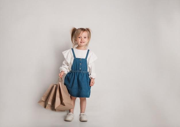 Красивая маленькая девочка в белой блузке и джинсовом сарафане с бумажными пакетами в руках