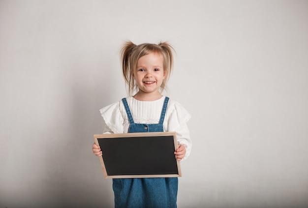Красивая маленькая девочка в белой блузке, джинсовом комбинезоне и графитовой доске