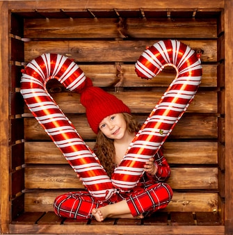 Красивая маленькая девочка в рождественской пижаме держит в руке большие карамельные конфеты на деревянном фоне