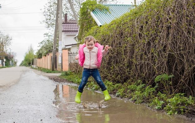 Красивая маленькая девочка в зеленых резиновых сапогах прыгает в лужи. съемка на ходу.