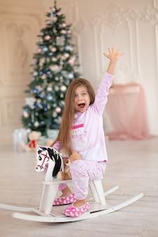 Красивая маленькая девочка в розовой пижаме радуется деревянной лошадке-качалке