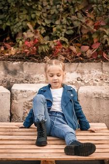 아름다운 어린 소녀가 나무 팔레트에 세련된 옷을 입고 앉아 있습니다. 파란색 재킷을 입은 세련된 아이. 캐주얼 스타일, 아이들을 위한 패션, 패셔너블한 슈트, 행복한 어린 시절