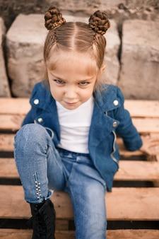 Красивая маленькая девочка сидит в стильной одежде на деревянных поддонах. стильный ребенок в синей куртке. повседневный стиль, мода для детей, модный костюм, счастливое детство