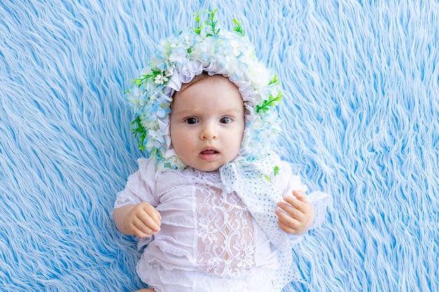 花で作られた帽子の青いふわふわの敷物の上に横たわって、カメラを見ている美しい少女