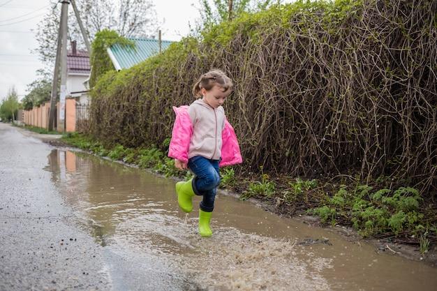 Красивая маленькая девочка ступила в лужу и брызгает водой. милая девушка в зеленых резиновых сапогах становится жесткой на улице.