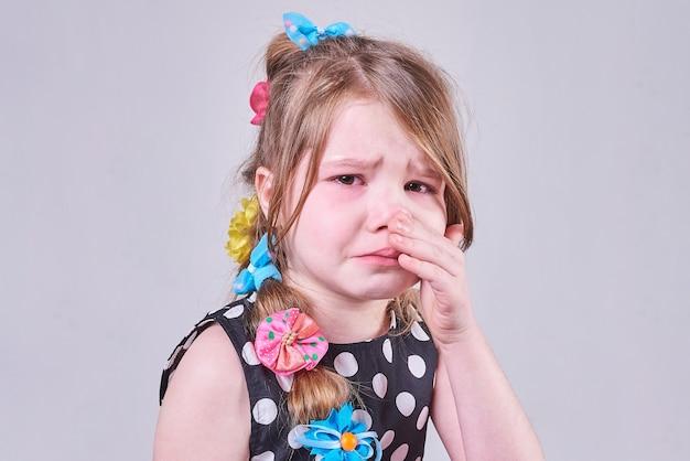 悲しそうな表情の美少女が泣き涙を手で拭く