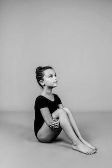 아름다운 작은 체조 선수가 고립된 배경에 앉아 있습니다. 흑백 사진