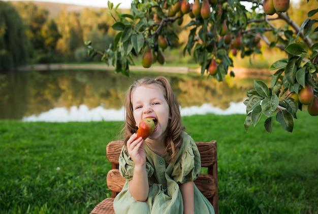 緑のドレスを着た美しい少女は梨の果実を食べています