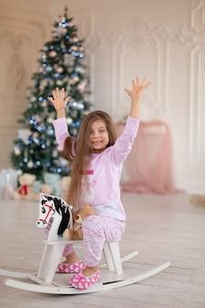 Красивая маленькая в пижаме радуется деревянной лошадке-качалке