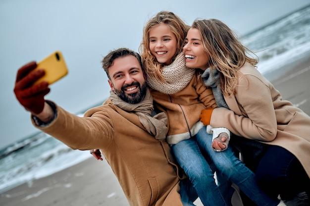 Красивая семейная пара и их очаровательная дочь обнимаются на берегу моря и зимой делают селфи, одетые в пальмы.