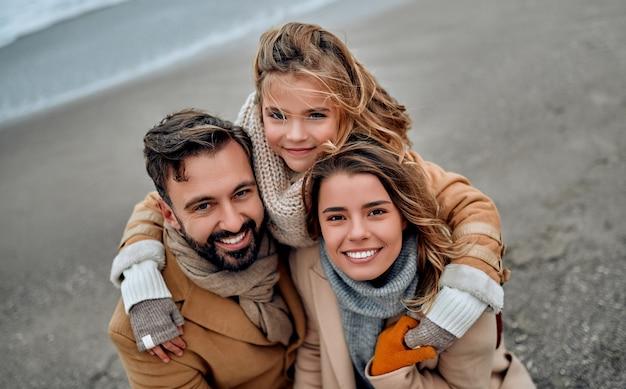 美しい夫婦とその素敵な娘が冬にコートを着て海岸で抱きしめています。