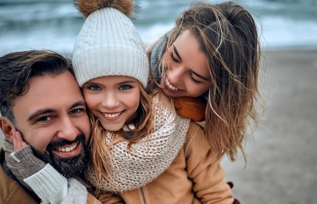 Красивая семейная пара и их очаровательная дочь обнимаются на берегу моря, зимой одетые в пальто.