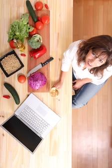 Красивая зрелая женщина режет на кухне с помощью компьютера.