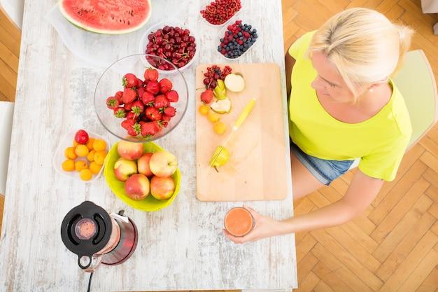 Красивая зрелая женщина, наслаждаясь смузи или соком с фруктами на кухне.