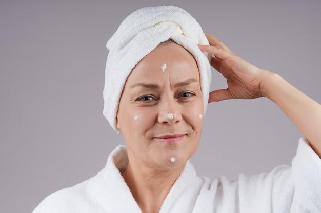 バスローブを着た美しい成熟した女性が、頭にタオルをつけて、栄養クリームを顔に塗ります。灰色の壁に隔離