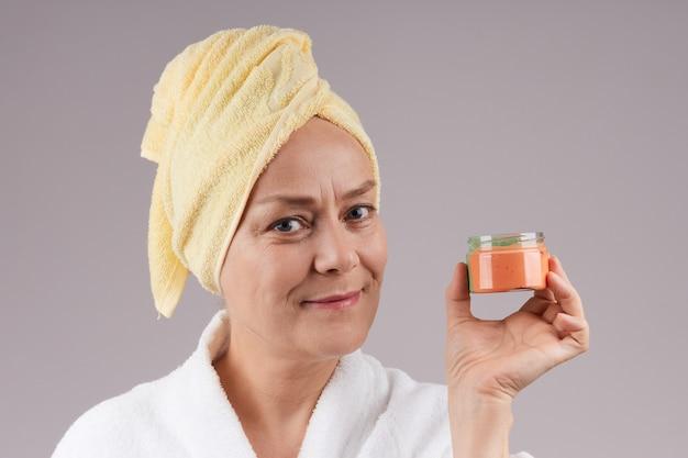 オレンジ色の栄養クリームの瓶を保持している白いコートを着た美しい成熟した女性。灰色の壁で隔離します。