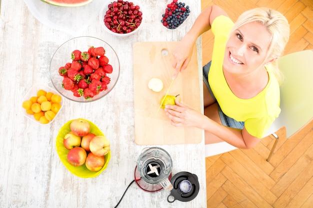 キッチンでスムージーやフルーツとジュースを準備する美しい成熟した女性。