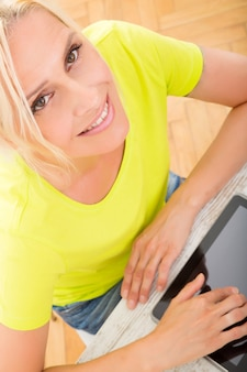Красивая зрелая женщина с коктейлем на кухне с помощью планшета.
