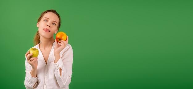 흰 셔츠를 입은 아름다운 중년 여성이 녹색 배경에 사과를 보여줍니다. 다이어트, 건강 식품, 채식주의의 개념. 배너. 텍스트에 대 한 장소입니다.