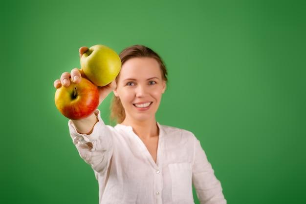 흰 셔츠를 입은 아름다운 중년 여성이 녹색 배경에 사과를 보여줍니다. 다이어트, 건강 식품, 채식주의의 개념.