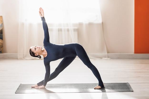 拡張された三角形の練習をしている自宅でヨガを練習している美しい中年の女性