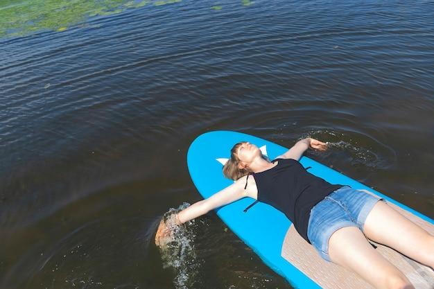 Красивая миллениальная девушка лежит на доске для серфинга с веслом и наслаждается отдыхом на природе.