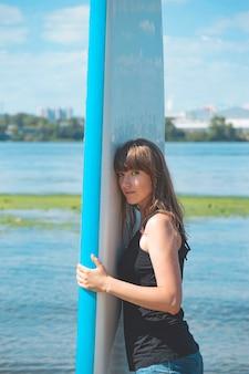 川岸に立っている間、彼女の手で鼻疽ボードを保持している美しいミレニアル世代の女性