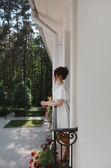 Красивая модельная девушка со свадебной прической в шелковом пеньюаре позирует на балконе утром ...