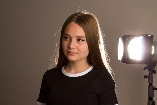 긴 금발 머리를 가진 아름다운 모델 소녀가 섬광에 비추어 스튜디오에서 포즈를 취하고, 윤곽 조명은 그녀의 머리에 그림자를 그립니다.