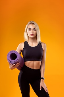スマートウォッチと黄色の背景に彼女の手にマットを持つスポーツウェアの美しいモデル