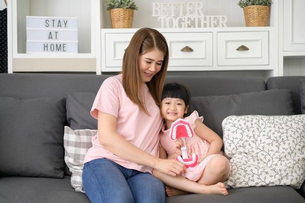 Красивая мать и дочь держат искусственную стоматологическую модель человеческой челюсти в доме, образовании и стоматологической концепции здоровья.