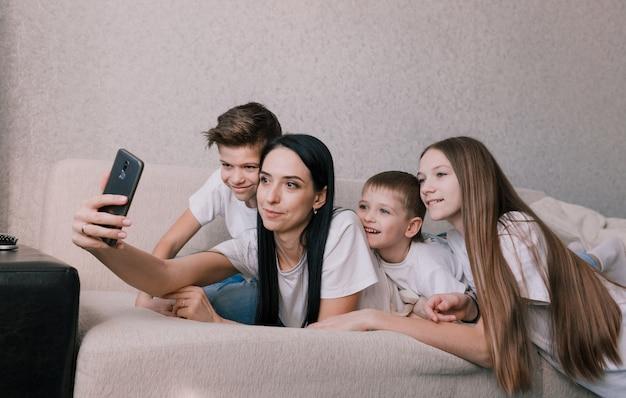 Красивая мама с детьми делает селфи на свой телефон, лежа на диване счастливая дружная семья