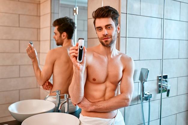 Красивый мускулистый мужчина в белом полотенце стоит в ванной перед зеркалом и бреет лицо. уход за лицом и телом.