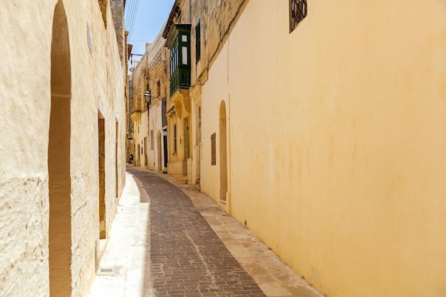 전형적인 몰타식 건축물이 있는 아름다운 좁은 길. 건물의 벽에는 성자의 석조 조각이 장식되어 있습니다.