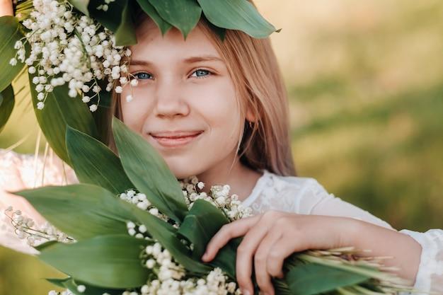 긴 흰 드레스에 긴 머리를 가진 아름다운 9 살짜리 금발 소녀, 계곡 꽃의 백합 꽃다발을 들고 공원에서 자연을 걷고 있습니다.