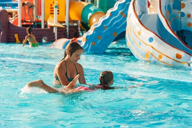 Красивая старшая сестра помогает младшей сестре научиться плавать в бассейне с чистой и прозрачной водой.