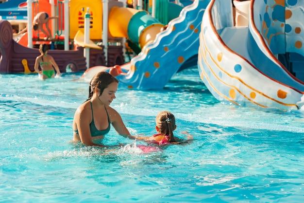 아름다운 언니가 여동생이 맑고 투명한 물로 수영장에서 수영하는 법을 배우도록 도와줍니다.