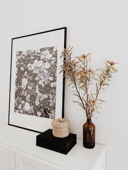 검은 색과 흰색 꽃과 검은 색 프레임이있는 아름다운 그림 흰색 서랍장에 서있는 유리로 만든 갈색 꽃병에 작은 짚 바구니 블랙 박스 말린 꽃