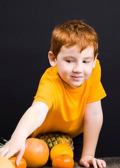 주스 또는 기타 음식이 준비된 감귤류 자몽을 곁들인 아름다운 유쾌한 빨간 머리 소년, 소년은 식탁에서 감귤류 과일을 먹고 놀아 기뻐합니다.