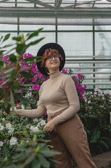 모자를 쓴 아름다운 플러스 사이즈 소녀가 온실의 녹색 식물들 사이에서 웃음
