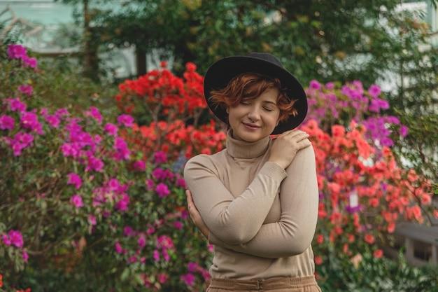 모자를 쓴 아름다운 플러스 사이즈 소녀가 온실의 녹색 식물 사이에서 미소 짓습니다.