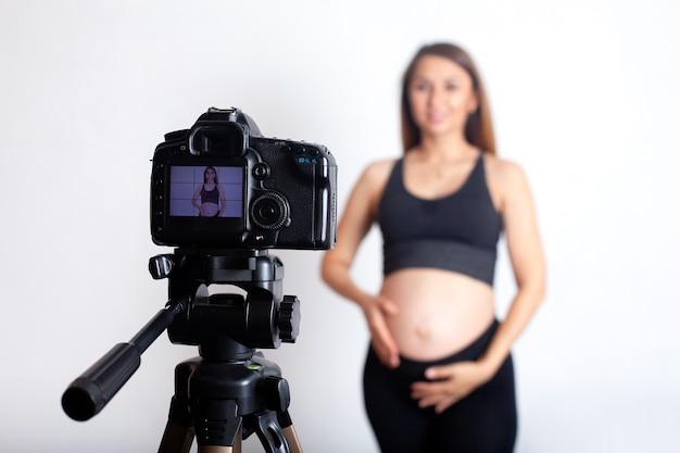 スポーツユニフォームを着た美しい妊婦が妊娠中のスポーツについてのビデオを撮影