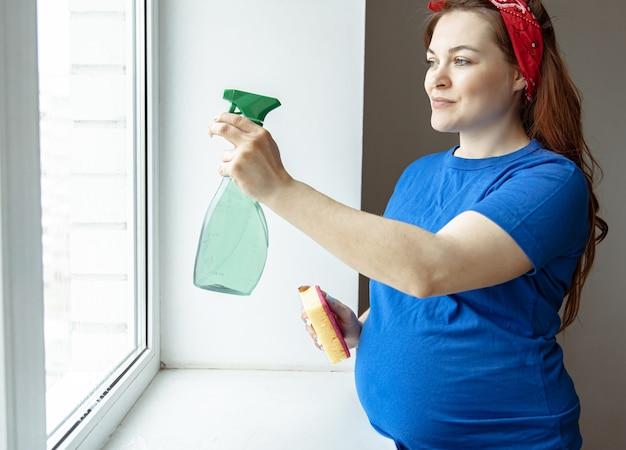 임신 마지막 달에 아름다운 임산부가 청소에 종사하고 창문을 닦습니다.