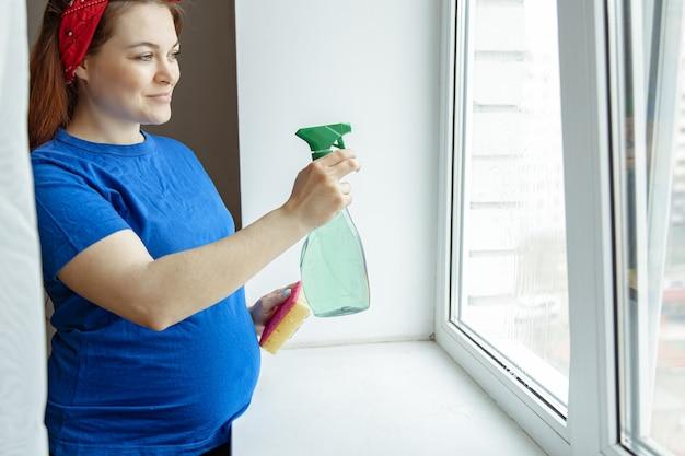 妊娠最後の数ヶ月の美しい妊婦は、窓の掃除と洗浄に従事しています。