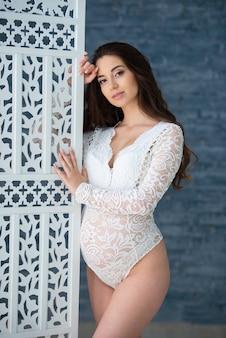 긴 물결 모양의 머리카락을 가진 아름다운 임산부는 투각 레이스 흰색 란제리 바디 슈트를 입은 병풍 뒤에 서 있습니다.