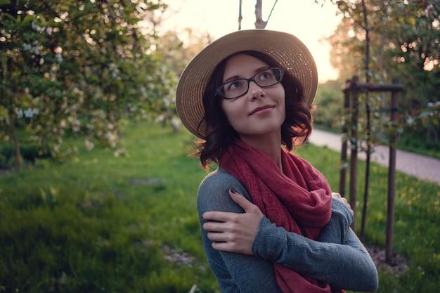 Красивая беременная молодая женщина наслаждается вечерней прогулкой по красивому зеленому парку. варшава, польша