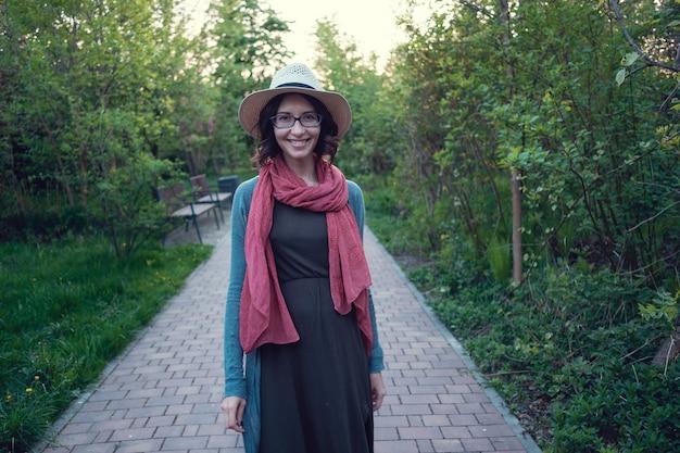 美しい妊娠中の若い女性は、美しい緑豊かな公園を散歩する夜を楽しんでいます。
