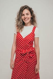 真っ赤な夏の美しい小学校の先生がまばゆいばかりの巻き毛の女の子をドレスアップ...