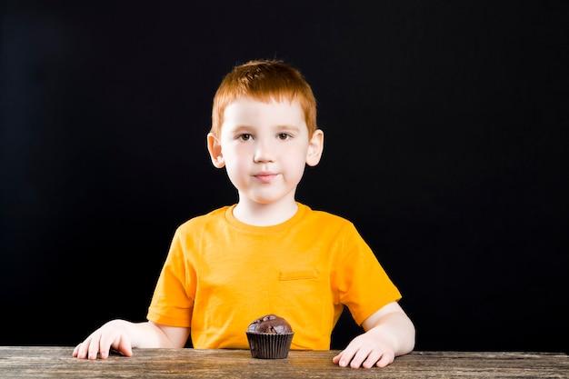 초콜릿 컵 케이크를 가진 아름다운 나가서는 소년, 소년은 기쁨으로 컵 케이크를 먹는다.