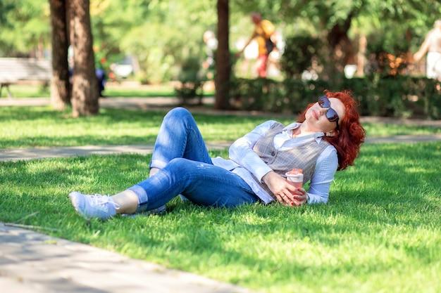 Красивая рыжеволосая женщина лежит в парке на лужайке с бутылкой воды
